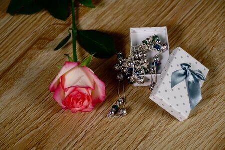 Dolce Vita Rosen mit gepunkteter weißer Geschenkbox auf Holzhintergrund