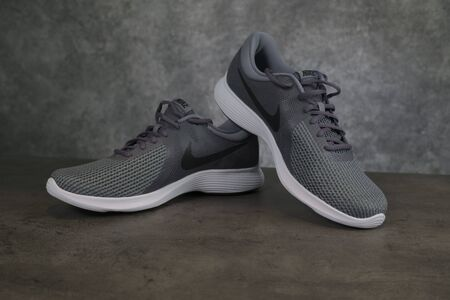 Tallinn, Estonia - 9.09.2019 : Product shoot of Nike mens running shoe. Nike revolution 4 on brown - grey background