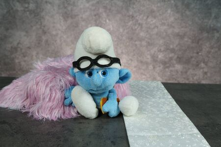 blue smurf with glasses on concrete table