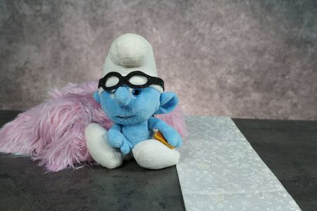 blue smurf with glasses on concrete table. photo