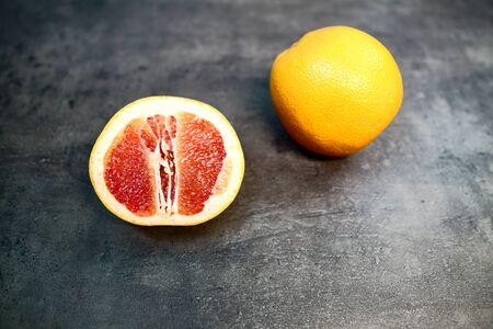 Grapefruit with grapefruit slice on grey background close up. Reklamní fotografie