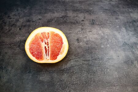 Grapefruit with grapefruit slice on grey background close up. Stock fotó