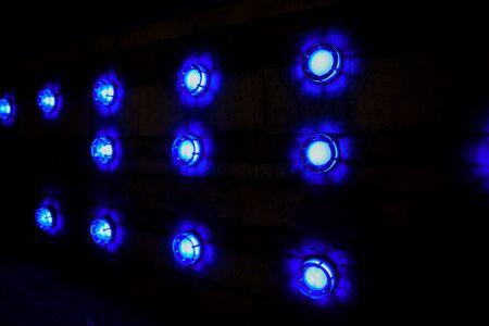 Round blue lamp, on dark background. closeup.