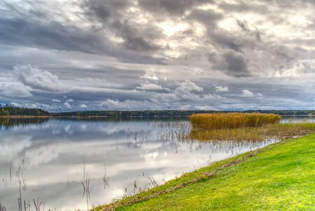 Beautiful cloudscape over the sea from green grass. Baltic Sea HDR