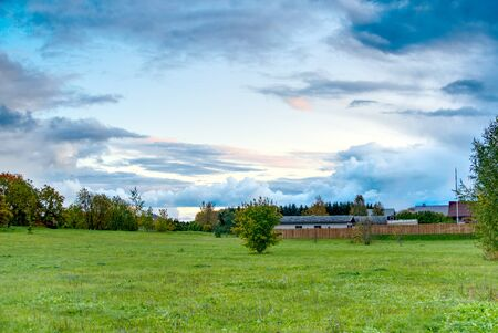 HDR landscape green meadow and clouds in the sky Фото со стока