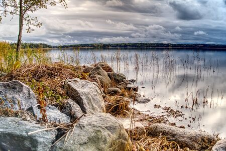 Pleasant landscape, nature, sea view. the sky in thick rain clouds, the rocky shore and the Baltic Sea like a mirror HDR Фото со стока