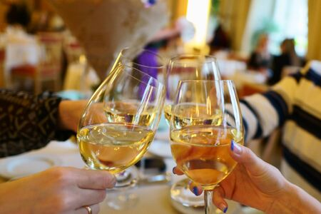 Wine glasses with white wine in a restaurant. People clink glasses of wine in a restaurant celebrating a birthday. hands without people