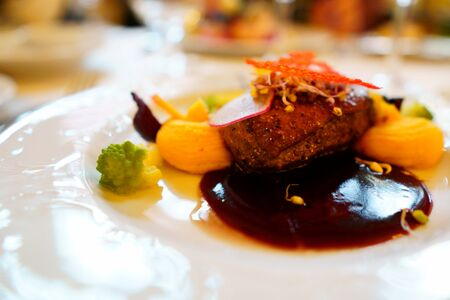 main course in the restaurant. The food is nicely laid on a white plate with a delicate pattern. mouth-watering dish and beautiful play of colors Фото со стока
