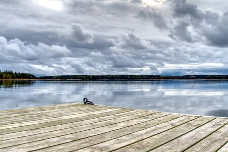 wooden pier for small boats, overlooking the pond and beautiful sky. blank for designers