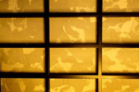 rectangular black metal grill on the wall, with a golden background.