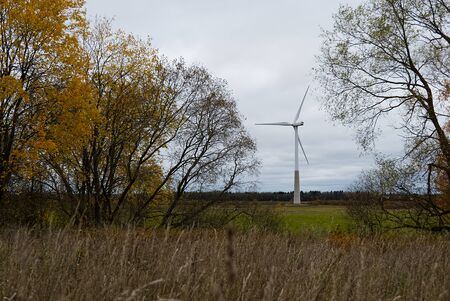 green electricity produced by wind generators against the backdrop of an autumn forest Фото со стока