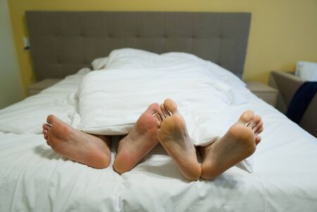 two pairs of legs in bed under a white blanket. Male and female lying feet on red bed together.