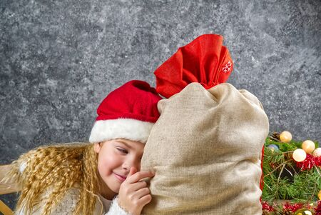 Little blonde girl in a gnomes red hat with santas bag in anticipation of a Christmas miracle. Фото со стока