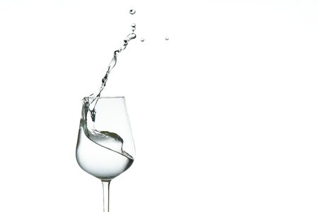 beautiful splashes of water in a wine glass, isolate on white, close up with copy space.