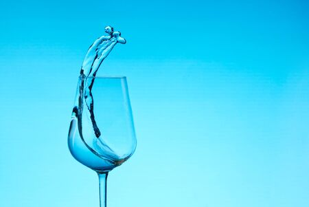 beautiful splashes of water in a wine glass, with blue filter, close up with copy space. Фото со стока