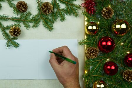 Hand writing Christmas letter on a natural linen bedspread. Eco Christmas is always in fashion. Can be used as postcards, backgrounds, wallpapers, posters. Christmas composition flat lay with Mockup.