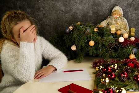 Little girl writes a letter to Santa Claus. Emotions: joy, happiness, thoughtfulness, fatigue ... Christmas should be hurried soon for Santa to make dreams come true