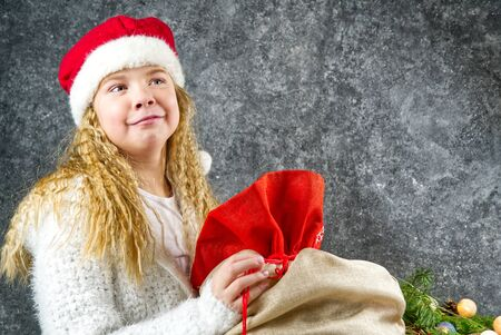 Little blonde girl in a red gnome hat Happy with a bag of gifts from Santa in anticipation of a Christmas miracle.
