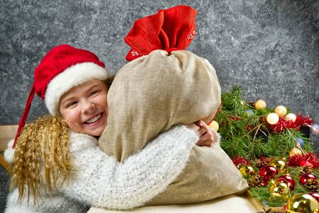 Little blonde girl in a gnomes red hat with santas bag in anticipation of a Christmas miracle hugs a bag with Christmas gifts