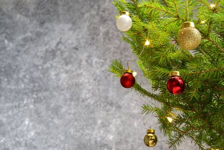 Beautiful Christmas composition. Decoration red and gold balls with spruce branch. Xmas backdrop for your greeting card with space for text.