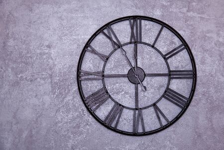 Vintage wall clock with roman numerals on the wall. gray stucco wall. Clock shows five to twelve 11:55