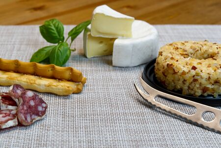 Cheese appetizer selection or Cheese and wine party table. Brie cheese, bread sticks and salami is great appetizer tostart your dinner. Stock fotó