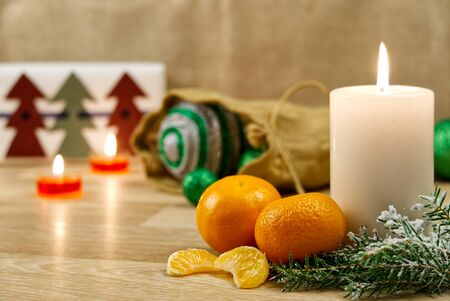Burning candles, christmas decorations and mandarin. Green balls for Christmas tree and fir twig on wooden floor with bokeh background. Copy space