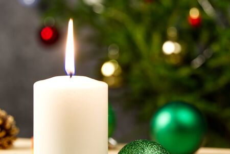Burning candles and christmas decorations. Green balls for Christmas tree and fir twig on wooden floor with bokeh background. Copy space