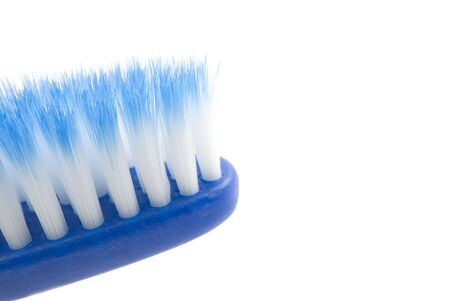 blue toothbrush with blue and white bristles. toothbrush close-up photo with copy space, isolated on white.