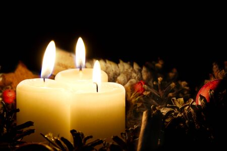 three burning candles with Christmas decoration from pine cones around Stock Photo