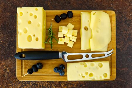 Flat lay of cheese cheese on a wooden board with knife photo