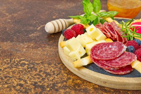 Meat and cheese plate antipasti snack with Prosciutto ham, Parmesan, Blue cheese, Cantaloupe melon and Olives on olive wood serving board on dark stone background. Banque d'images