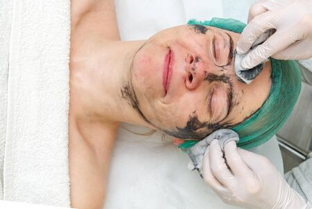Beautician washes off a natural moisturizing mask on the face of a young beautiful woman. Black bamboo mask. Close up photo