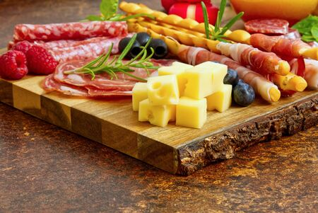 Meat and cheese plate antipasti snack with Prosciutto ham, Parmesan, Blue cheese, Cantaloupe melon and Olives on olive wood serving board on dark stone background.