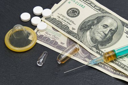 Money and pills with drugs and a syringe on the medical table. Stock Photo