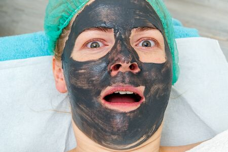 Young woman in a beauty salon with a black mask on her face. The concept of cosmetology. The cosmetologist performs a procedure to cleanse the face with problem skin.