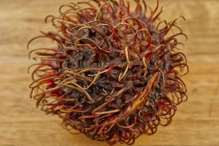 Fresh Fruits, Ripe and Sweet Refreshing Rambutan Served on A Wooden board, closeup photo