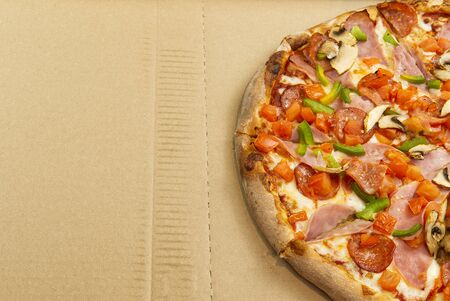 Flat lay of tasty italian pizza on on cardboard box. Cheese and peppers. Delicious food. photo can be used for pizzeria menu