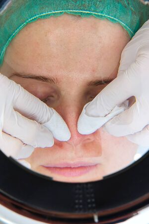 Beautician removes - squeezes acne from the face of a young beautiful girl. The concept of cosmetology. The cosmetologist performs the procedure to cleanse the face with problem skin. under cosmetic magnifying glass.