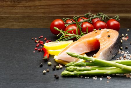 fresh raw salmon steaks with pepper corns, salt, lemon and olive oil on black background. Healthy food, diet concept. Preparation for cooking fish with spices