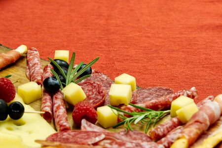 Meat and cheese plate antipasti snack with Prosciutto ham, Parmesan, Blue cheese, Cantaloupe melon and Olives on olive wood serving board on red background