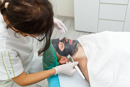 Beautician applies natural moisturizing mask to the face of a young beautiful woman. Black bamboo Charcoal Face Mask, applied to the face with a brush.