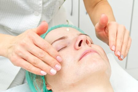 Beautician applies a natural moisturizing mask to the face of a young beautiful woman. Anti-aging mask and wrinkles for problem skin. Cosmetology concept. The cosmetologist performs the procedure to cleanse and moisturize the face.