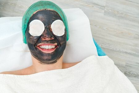 Young woman in a beauty salon with a black mask on her face. The concept of cosmetology. The cosmetologist performs a procedure to cleanse the face with problem skin