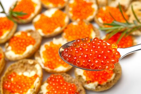 Sandwiches with red caviar on white plate close up