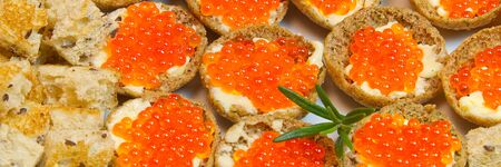 Sandwiches with red caviar on white plate close up. panoramic shoot Stock fotó