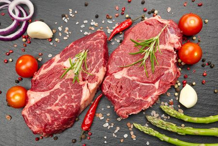 Raw rib eye steak with spices and vegetables. Ingredients for restaurant meal. Fresh meat, salt, rosemary, thyme, chilli, cherry tomatoes, garlic on black stone. Food background.