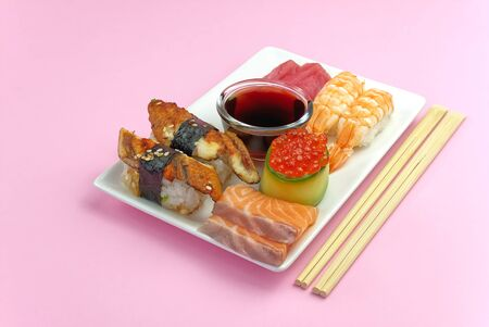 traditional japanese sushi set on a white plate isolated on a pink background. tasty set of sushi, nigiri, sahimi and maki. delicious dinner or lunch for one person. Banque d'images