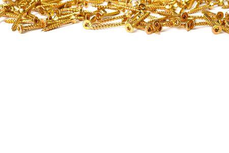 Gold screws scattered randomly on a white background. Torx yellow zinc head screws