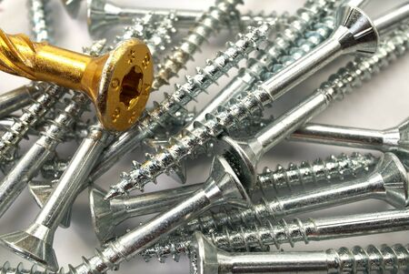 Gold screws for wood, chipboard or plywood with torx head. Torx screws close up. 写真素材